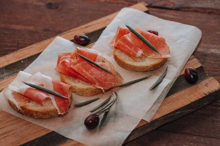 Sandwiches with prosciutto and fresh olives on a wooden board. Close up