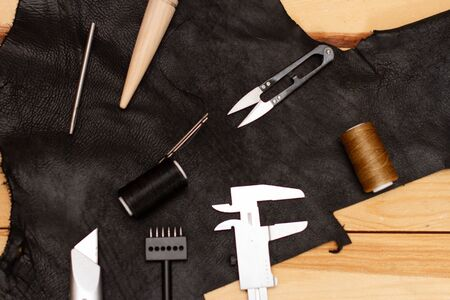 Set of leather work tools on black leather and wooden boards Zdjęcie Seryjne