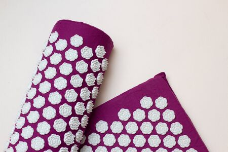Acupressure mat and pillow on white background