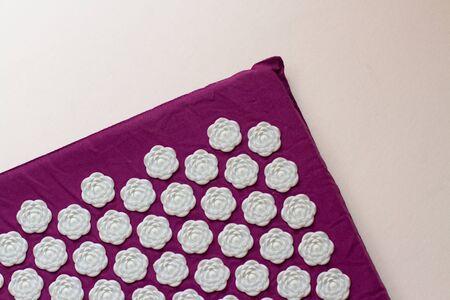 Tapis d'acupuncture pour massage sur fond blanc. Traitement de médecine alternative. Banque d'images