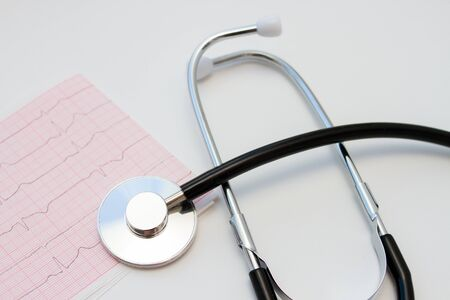 Stethoscope and ECG cardiogram report on white background