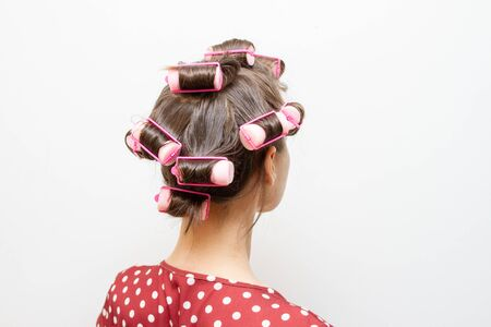 Plastic curlers for curling hair on the head of a brunette girl.