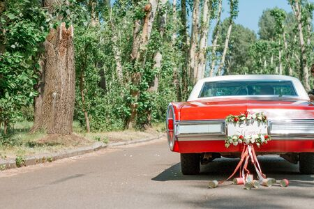 A retro car decorated for a wedding with the words just married and tin cans on ribbons. Wedding decorations outdoor. Beautiful wedding car with plate Just Married.