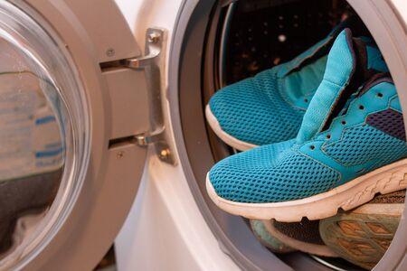 Blue sneakers into washing machine, automatic washing machine.