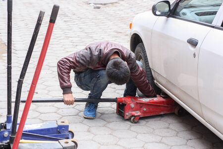 A man replaces the wheels on a car with tire fitting jack. Reklamní fotografie