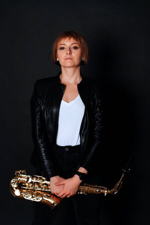 Saxophonist woman in leather jacket with her musical saxophone. Stock fotó