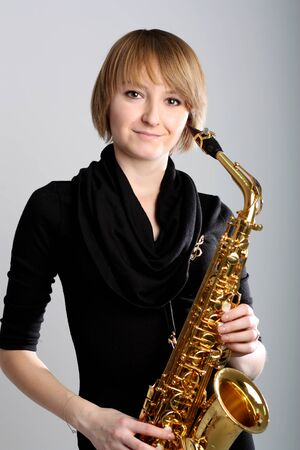 Young girl Jazz musician Saxophonist with her musical saxophone.