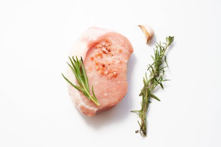 Red pork steak with garlic and rosemary on white background. Top view. Soft Focus Фото со стока