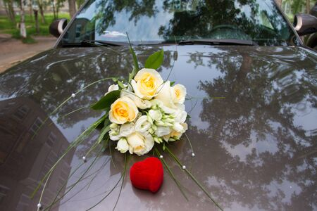 Wedding bouquet on the hood of the car and a red box with rings.