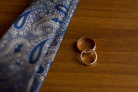 Wedding rings and tie of the groom. Selective focus.