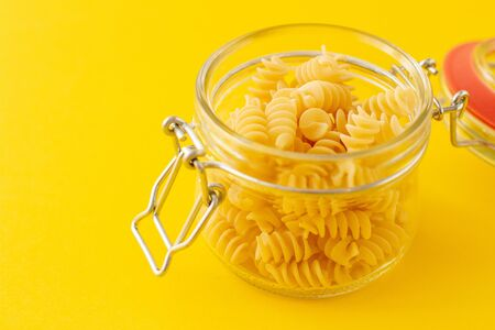 Dried italian pasta spiral Fusilli in a open glass jar on yellow background