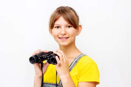 Little child girl looking through binoculars. Adventure concept