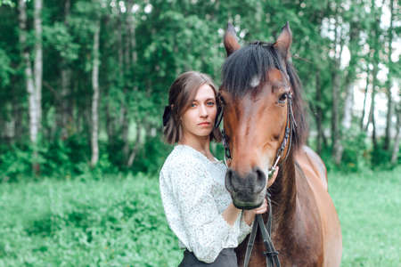 Portrait young woman with horse in forest. Brunette girl and horse