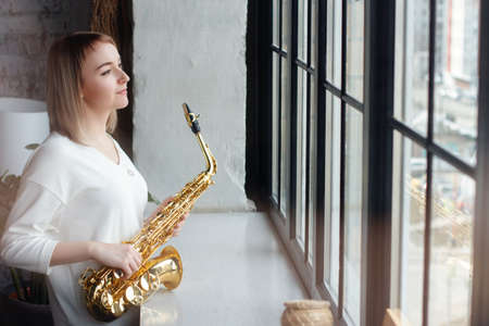 Young woman saxophonist with an instrument stands by the window. Cozy home interior. Blonde girl with a saxophone. Soft focus. 写真素材