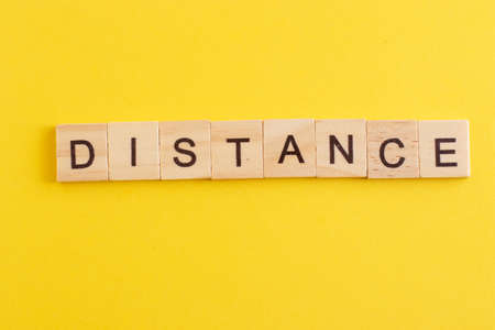 Word DISTANCE made from wooden letters on yellow background.