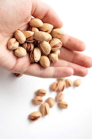 Heap of Pistachio nuts. Handful of pistachios in hand. Standard-Bild