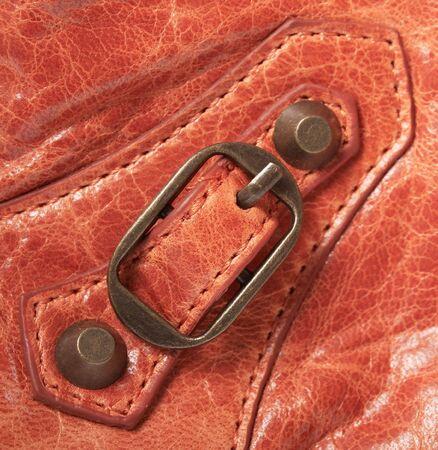 metal fastener: Metal fastener close up on an orange leather