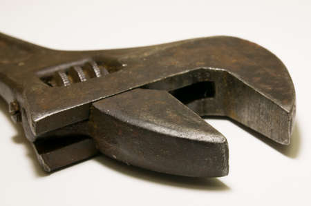 Old fashion adjustable wrench closeup on White.