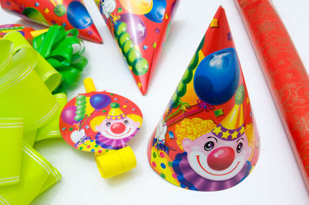 blowers: Party props over white background. Party hats, party blowers and paper streamers. Stock Photo