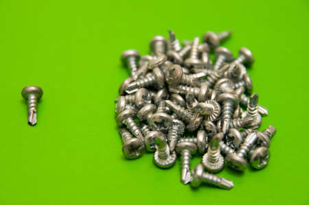 conjoin: The one screw and a pile of screws on green background.
