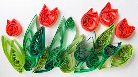 lea: Childrens crafts tulip is made from strips of colored paper on textured white background.
