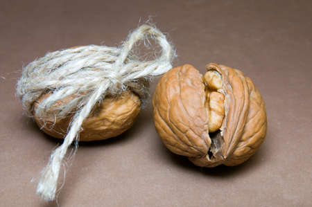 Walnut tied with twine and cracked walnuts on a brown background gray shade 版權商用圖片