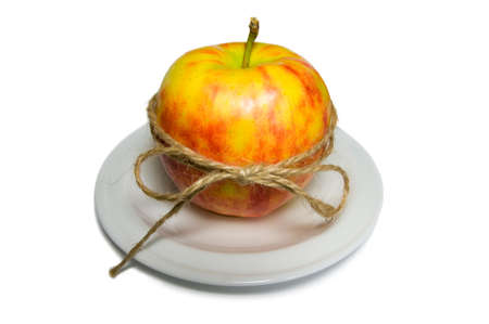 Apple tied with twine on a white plate closeup
