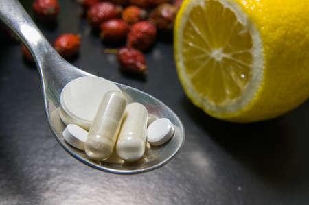 drug use: Pills in a spoon versus lemon and hips with black gradient background. Pills vs lemon and hips symbolizing choice between healthy diet and frequent drug use. Selective focus on pills. Stock Photo
