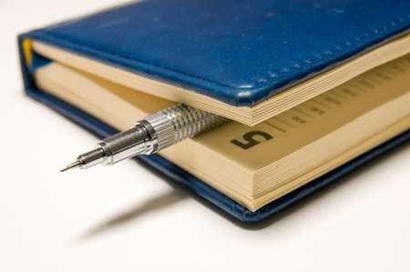 silvery: Blue diary with a silvery mechanical pencil between the pages inside.