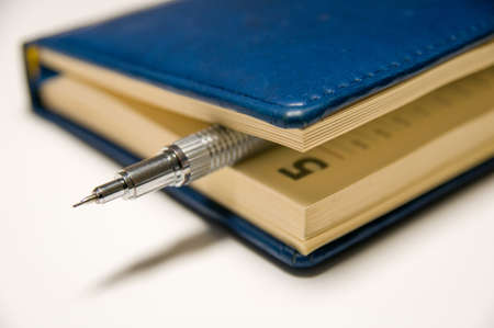 silvery: Blue diary with a silvery mechanical pencil between the pages inside focus at pencil. Stock Photo
