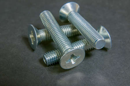 silvery: Silvery four bolts on grey. Four bolts grid focus at centre. Stock Photo
