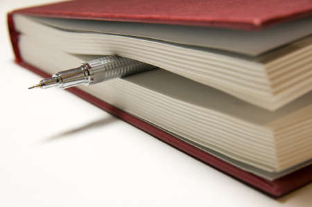 silvery: Silvery mechanical pencil between the pages of a closed red book.
