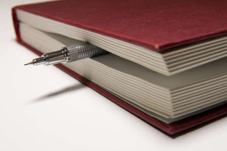 silvery: Closed red book with a silvery mechanical pencil between the pages inside.