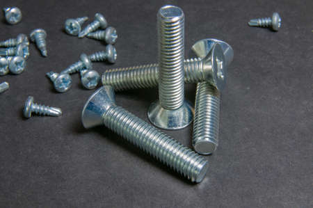 silvery: Silvery four bolts and pile screws on grey. Centre upright bolt with triangle bolt.