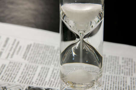 transience: Completely filled sandglass on newspaper with black gradient background. Sandglass on newspaper. Symbolizing the transience of time, the need for timely decision also enthusiastic Read, think, do attitude.