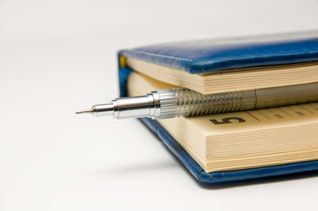 silvery: Silvery mechanical pencil between the pages of a closed blue diary. Stock Photo