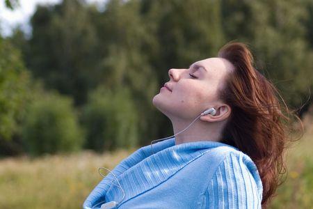 musicoterapia: Rilassata giovane donna ascolto musica nel parco  Archivio Fotografico