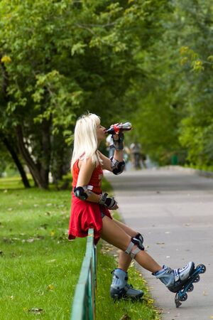Adult woman on rollerskates stopping for a drink photo