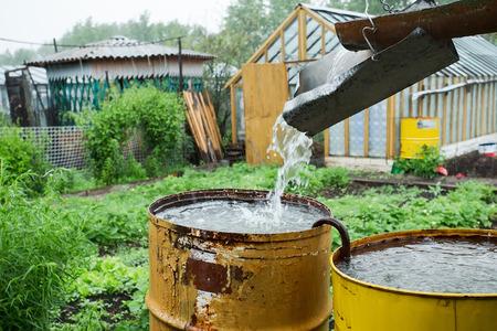 tuberias de agua: tuber�a de drenaje de la casa y el barril oxidado oxidado Foto de archivo