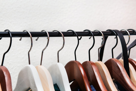 clothes rack: Clothes hang on a shelf in home
