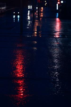 Car light is reflected on the wet asphalt