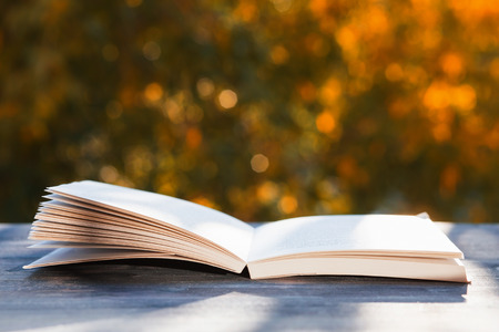 open book on wooden table, background of autumn trees