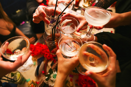 cheer: Clinking glasses with alcohol and toasting, party Stock Photo