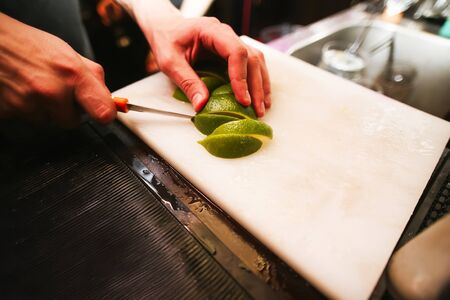 paring knife: Hands with a paring knife slicing a lime