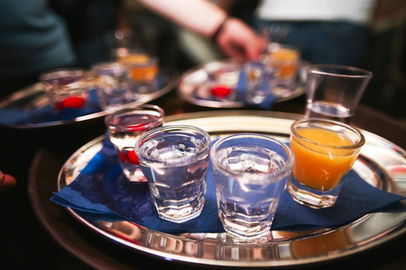 cocktail bar: Several shot glasses on silver tray in bar setting