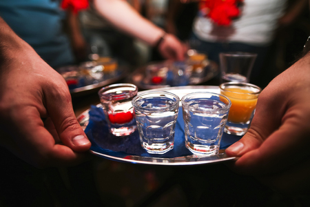 silver bar: Several shot glasses on silver tray in bar setting