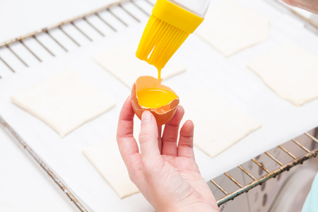 smearing: Smearing egg pie. Cooking sweet pastries. Hands Stock Photo