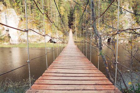 bridge over water: narrow pedestrian bridge over water. autumn leaves