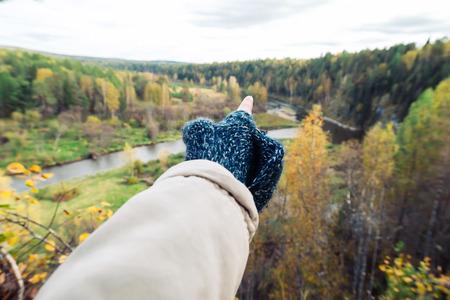 自然の中で遠くに指している女性ハイカー