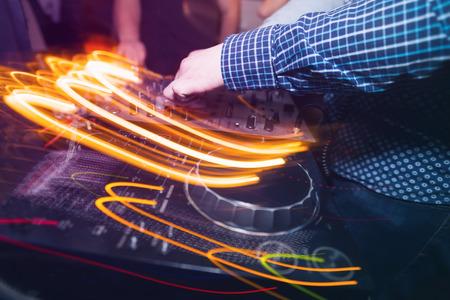 club dj: Club DJ playing mixing music on vinyl turntable at party